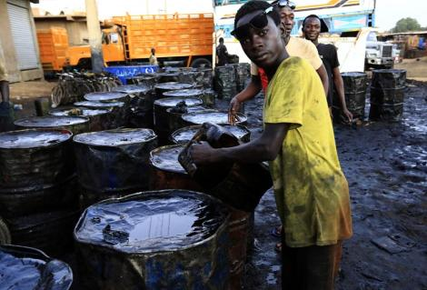 Young men work at a collection point for recycled oil in the capital Khartoum